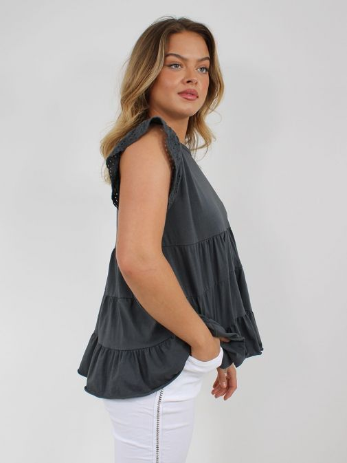 side shot of the Cilento Women Ruffle Detail Top in the Grey featuring cap sleeves with Broderie Anglaise detailing, rounded neckline and ruffle detailing to the bottom of the top