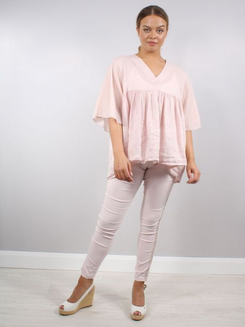 Model wearing Cilento Woman Diamante Denim Joggers in Pink paired with angel sleeve linen top