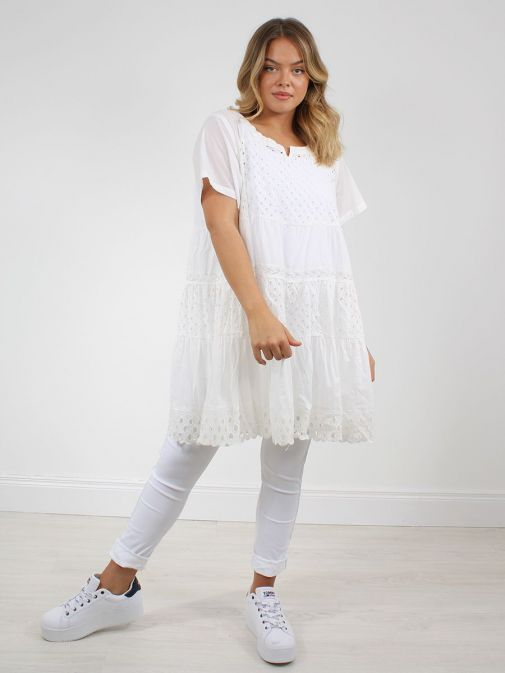 Front shot of the Cilento Woman Broderie Anglaise Dress White featuring a round neckline with a slight v opening, short sleeves and knee lenght