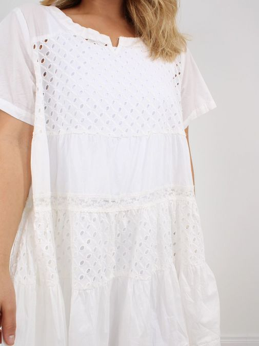 closeup shot of the Cilento Woman Broderie Anglaise Dress White featuring a round neckline with a slight v opening, short sleeves and knee-length