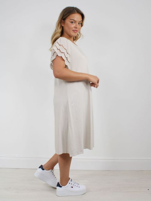 side shot of the Cilento Woman Broderie Butterfly Sleeve Dress in the Beige colour featuring broderie short sleeves, rounded neckline and a midi length