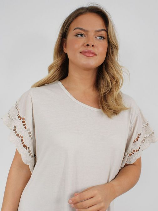 closeup shot of the Cilento Woman Broderie Butterfly Sleeve Dress in the Beige colour featuring broderie short sleeves, rounded neckline