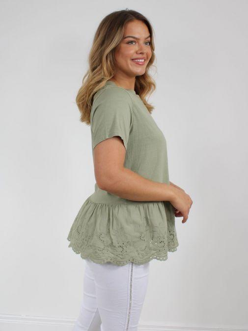 Side on shot of model wearing Cilento Woman Broderie Frill Hem Top in Green