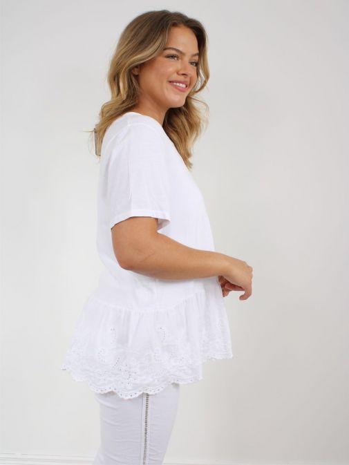 Side shot of model wearing Cilento Woman Broderie Frill Hem Top in White