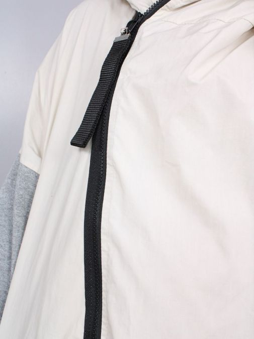 closeup shot of the Cilento Woman Hooded Longline Jacket in the Cream and Grey featuring black zip, long sleeves