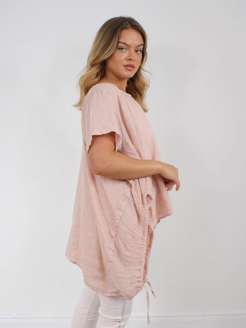 side shot of the Cilento Woman Linen Drawstring Top in the Peach colour featuring short sleeves, rounded neckline, pull cords to each side