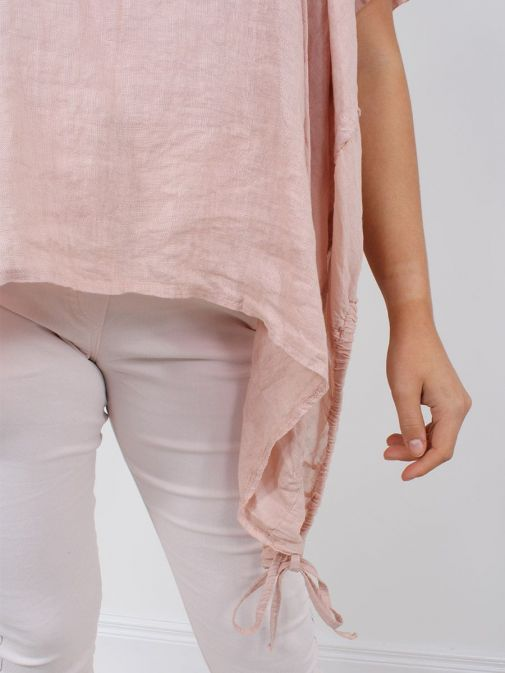 closeup shot of the Cilento Woman Linen Drawstring Top in the Peach colour featuring pull cords to each side