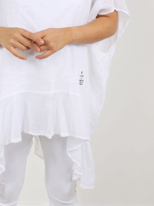close up of model wearing Cilento Woman Linen Frill Hem Tunic in White