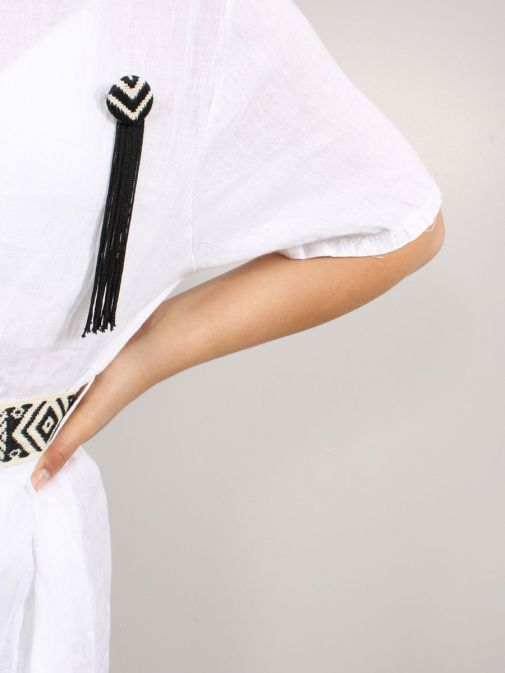 Close up of brooch as part of the Cilento Woman Linen Midi Dress in White