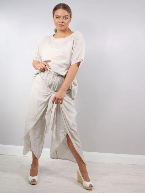 Model wearing Cilento Woman Wrap Leg Linen Trousers in Natural