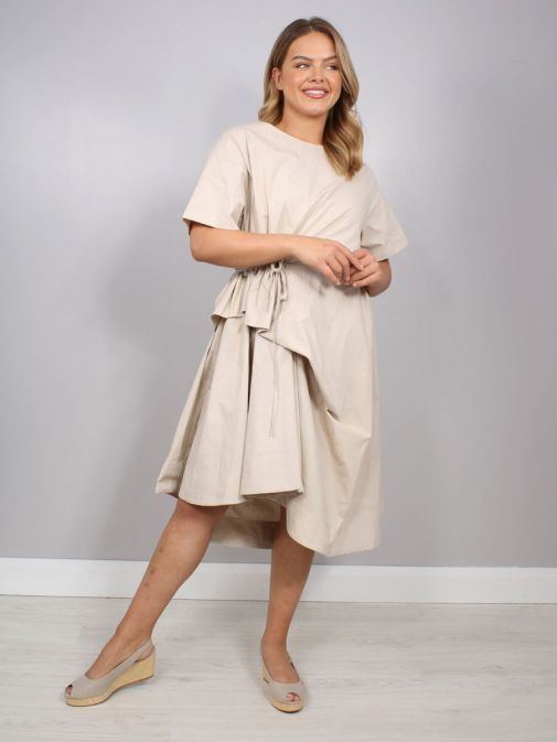 Front shot of the Cilento Women Short Sleeve Dress in the Beige colour featuring a rounded neckline, short sleeves, pull cord waist and dropped and asymmetric hem