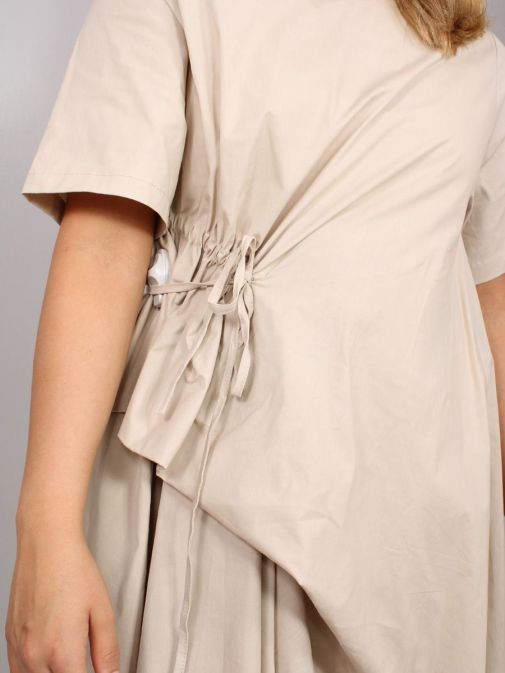 closeup shot of the Cilento Women Short Sleeve Dress in the Beige colour featuring a short sleeves, pull cord waist and dropped and asymmetric hem