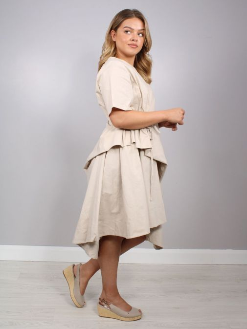 side shot of the Cilento Women Short Sleeve Dress in the Beige colour featuring a rounded neckline, short sleeves, pull cord waist and dropped and asymmetric hem