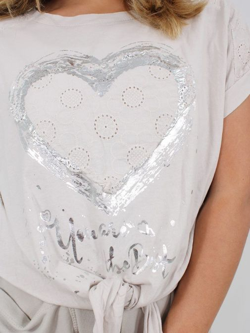 closeup shot of the Cilento Women Silver Heart Detail Top in the Beige colour featuring short sleeves, rounded neck and silver heart