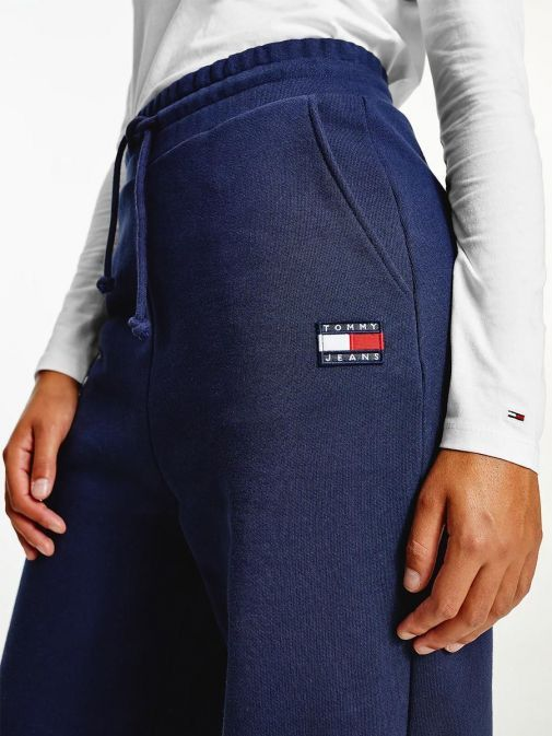 Close up shot of model wearing Tommy Jeans Badge Relaxed Joggers in Navy