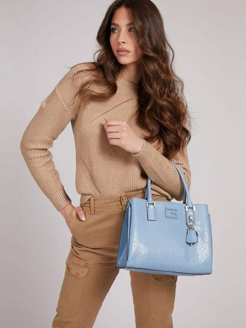 Model holding Guess Blane 4G Logo Patent Handbag in Blue