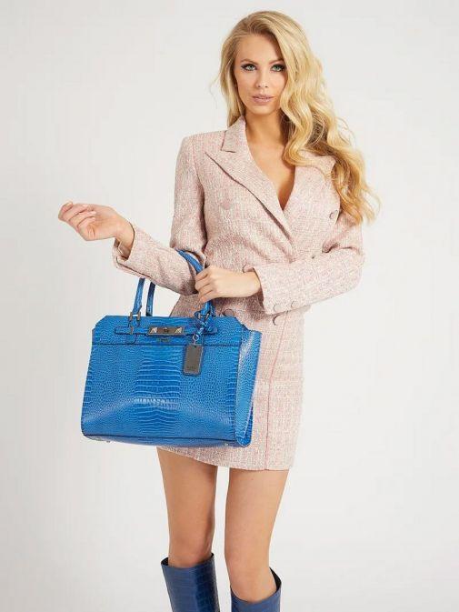 Model holding the Guess Raffie Croc Print Handbag in Royal Blue