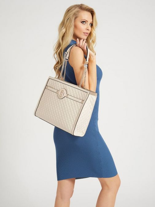 Model holding Guess Heyden Quilted Shopper in Stone