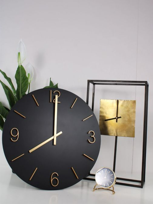 Picture of Large Round Wall Clock in Black and Gold with a two more clocks and a plant