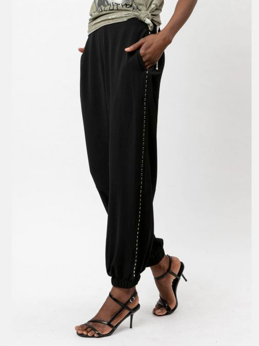 side shot of the Religion Outlook Trousers in the Black featuring elasticated waist, ankle cuffs, pockets and studded detail down the side