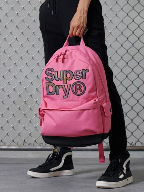 Model holding Superdry Rainbow Infill Montana Backpack in Pink