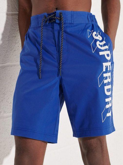 Model wearing Superdry Classic Board Shorts in Cobalt Blue for men