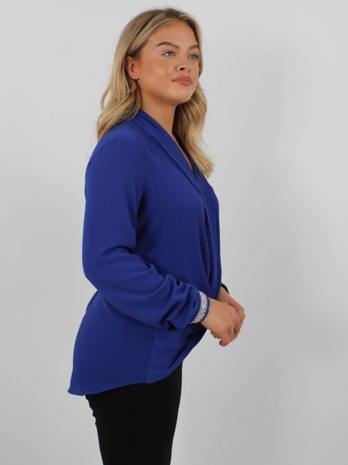 Model wearing Tia Knot Effect Blouse in Blue showing dipped hem at back