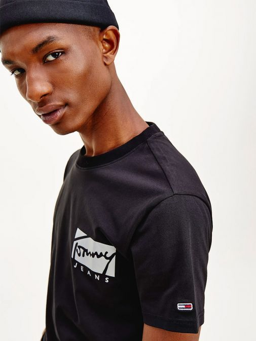 side shot of the Tommy Jeans Script Logo Stretch Organic Cotton T-Shirt in the Black Colour featuring the logo, short sleeves and round neckline