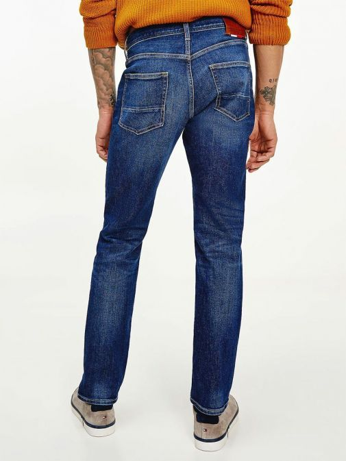 Back shot of model wearing Tommy Hilfiger Denton Straight TH Flex Jeans in Kima Indigo