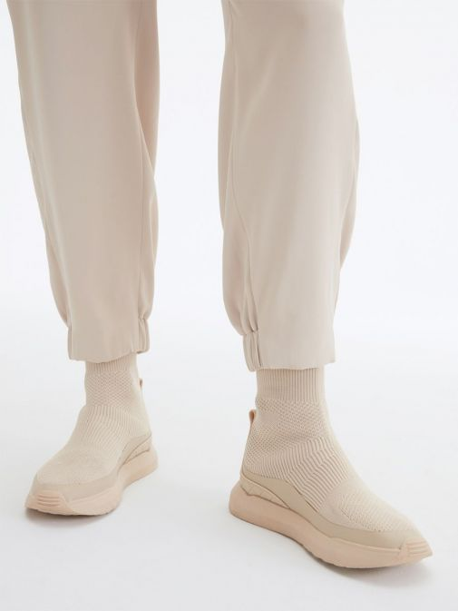 closeup of the Uchuu Elastic Waisted Trousers in the Beige featuring elasticated ankle cuffs