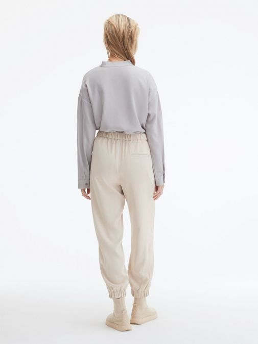 back shot of the Uchuu Elastic Waisted Trousers in the Beige featuring pockets, elasticated waistband and ankle cuffs