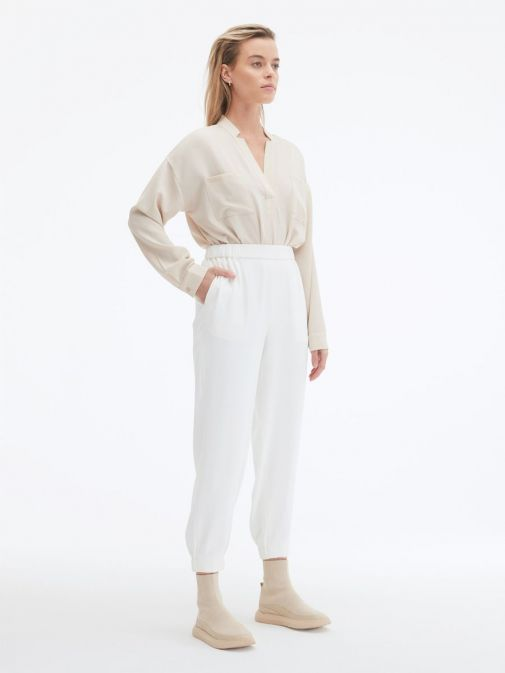 side shot of the Uchuu Elastic Waisted Trousers in the Beige featuring pockets, elasticated waistband and ankle cuffs