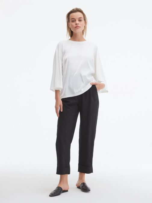 Full shot of model wearing Uchuu Flare Sleeve Top in Cream with black trousers