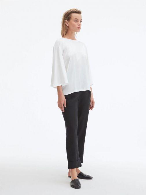 Side shot of model wearing Uchuu Flare Sleeve Top in Cream