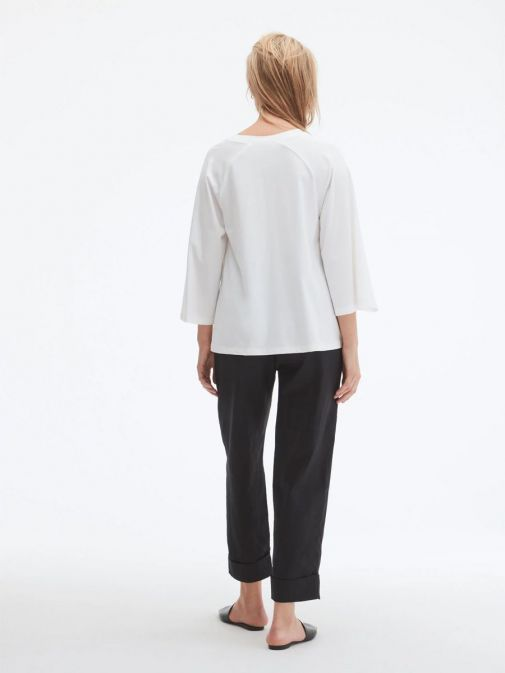 Back shot of model wearing Uchuu Flare Sleeve Top in Cream