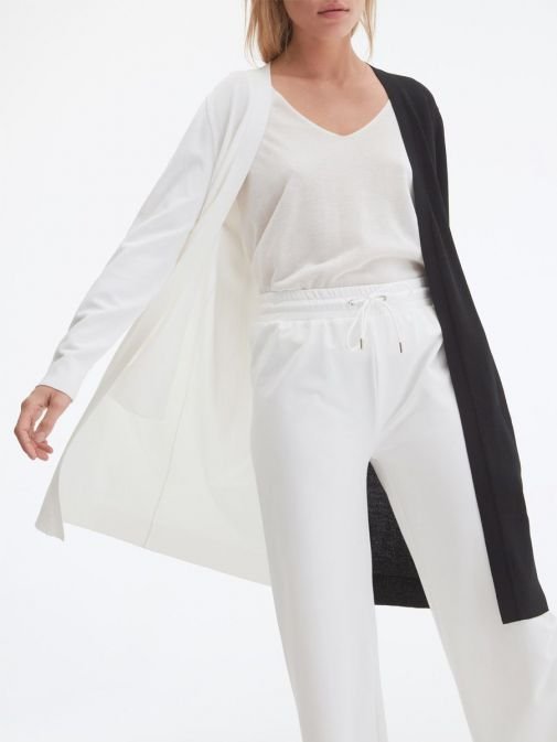 closeup of the Uchuu Longline Cardigan in White and Black featuring pockets, long sleeves and contrasting block colours