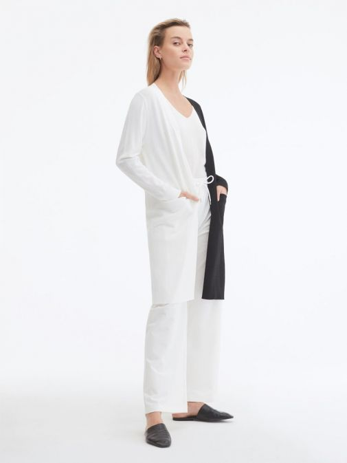 side shot of the Uchuu Longline Cardigan in White and Black featuring pockets, long sleeves and contrasting block colours