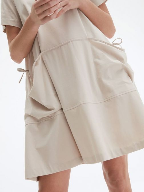 closeup shot of the Uchuu Round Neck Dress in the Beige colour featuring a large kangaroo pocket to the front, short sleeves