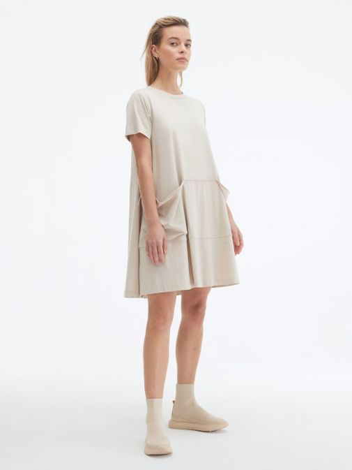 side shot of the Uchuu Round Neck Dress in the Beige colour featuring a large kangaroo pocket to the front, short sleeves and a rounded neckline