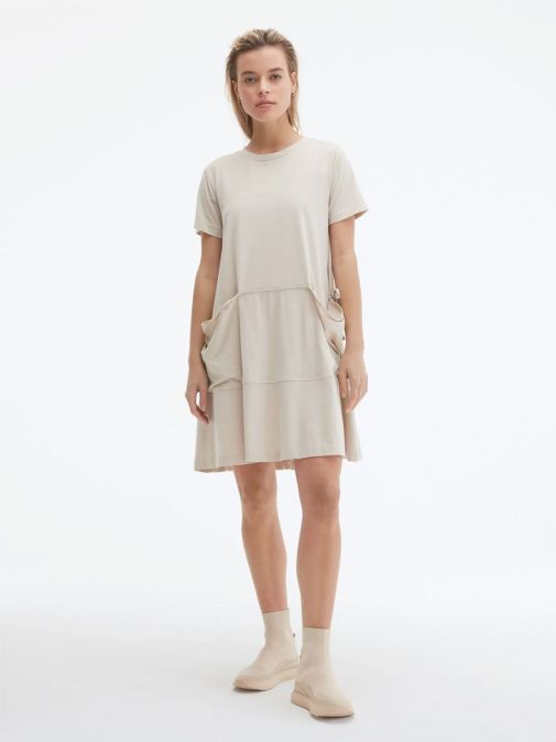 Front shot of the Uchuu Round Neck Dress in the Beige colour featuring a large kangaroo pocket to the front, short sleeves and a rounded neckline
