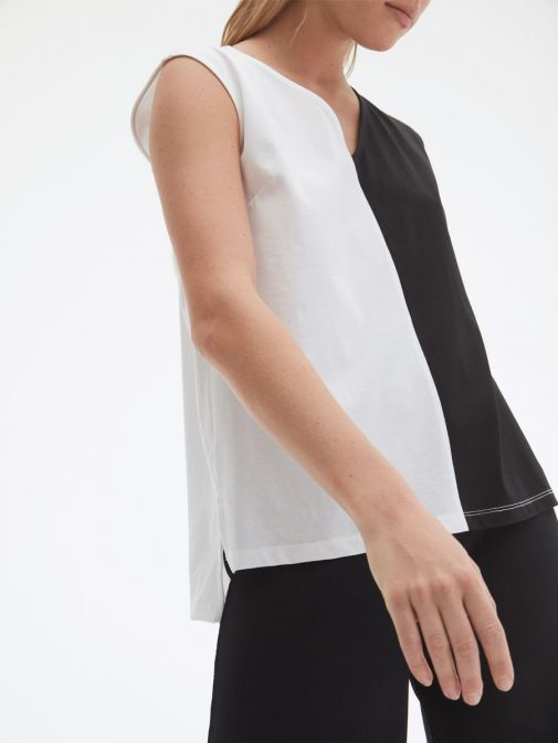 side shot of the Uchuu Vest Top in Black and White featuring v-neckline, Contrasting white stitching, color block effect and dropped hem to the back