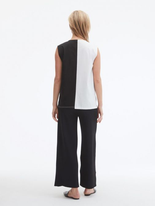 back shot of the Uchuu Vest Top in Black and White featuring v-neckline, Contrasting white stitching, colour block effect and dropped hem to the back