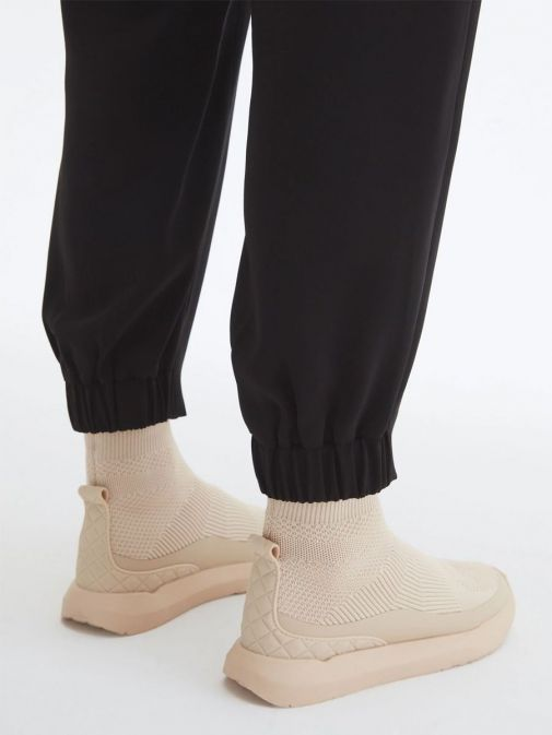 Close up of cuffed trousers legs of Uchuu Elastic Waisted Trousers in Black