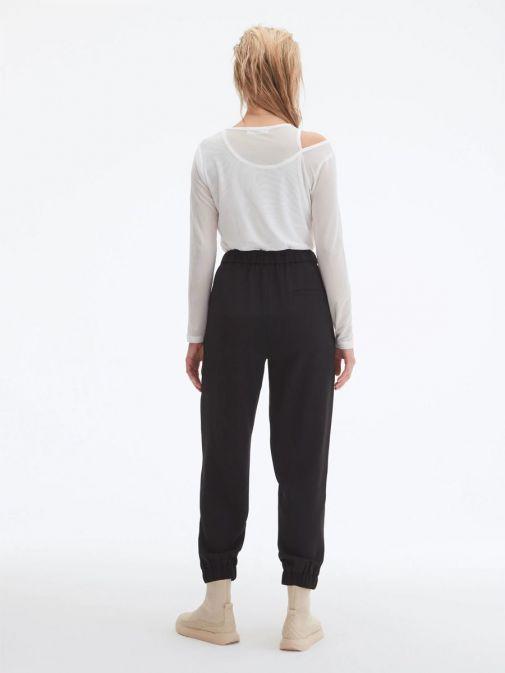 Back shot of model wearing Uchuu Elastic Waisted Trousers in Black