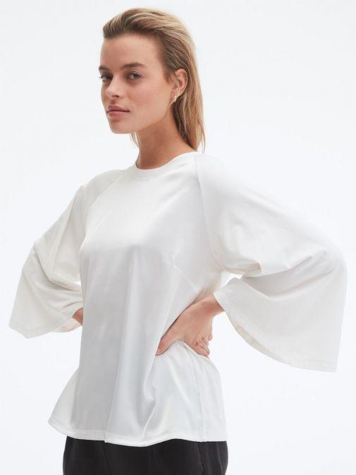 Model wearing Uchuu Flare Sleeve Top in Cream