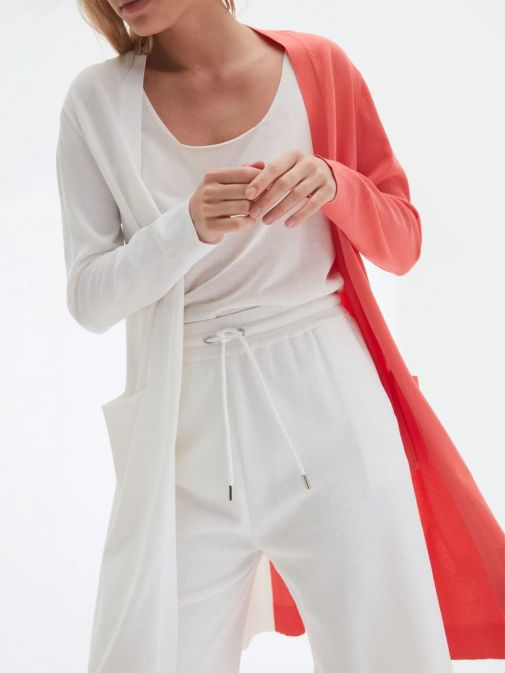 Close up of model wearing Uchuu Longline Cardigan in White and Strawberry