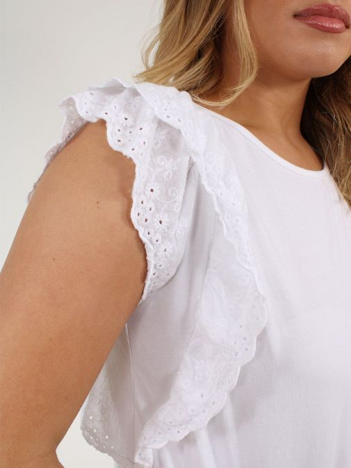 closeup shot of the Cilento Woman Broderie Frill Sleeve Top in the White colour featuring a rounded neckline and frill sleeve detailing
