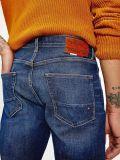 close up of model wearing Tommy Hilfiger Denton Straight TH Flex Jeans in Kima Indigo